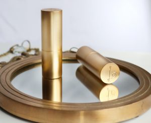 Two gold round lipstick cases placed on a round gold mirror, giving a reflective effect. The lipstick have a L and a pair of lips etched into the lips, this is the logo for Lisa Eldridge.