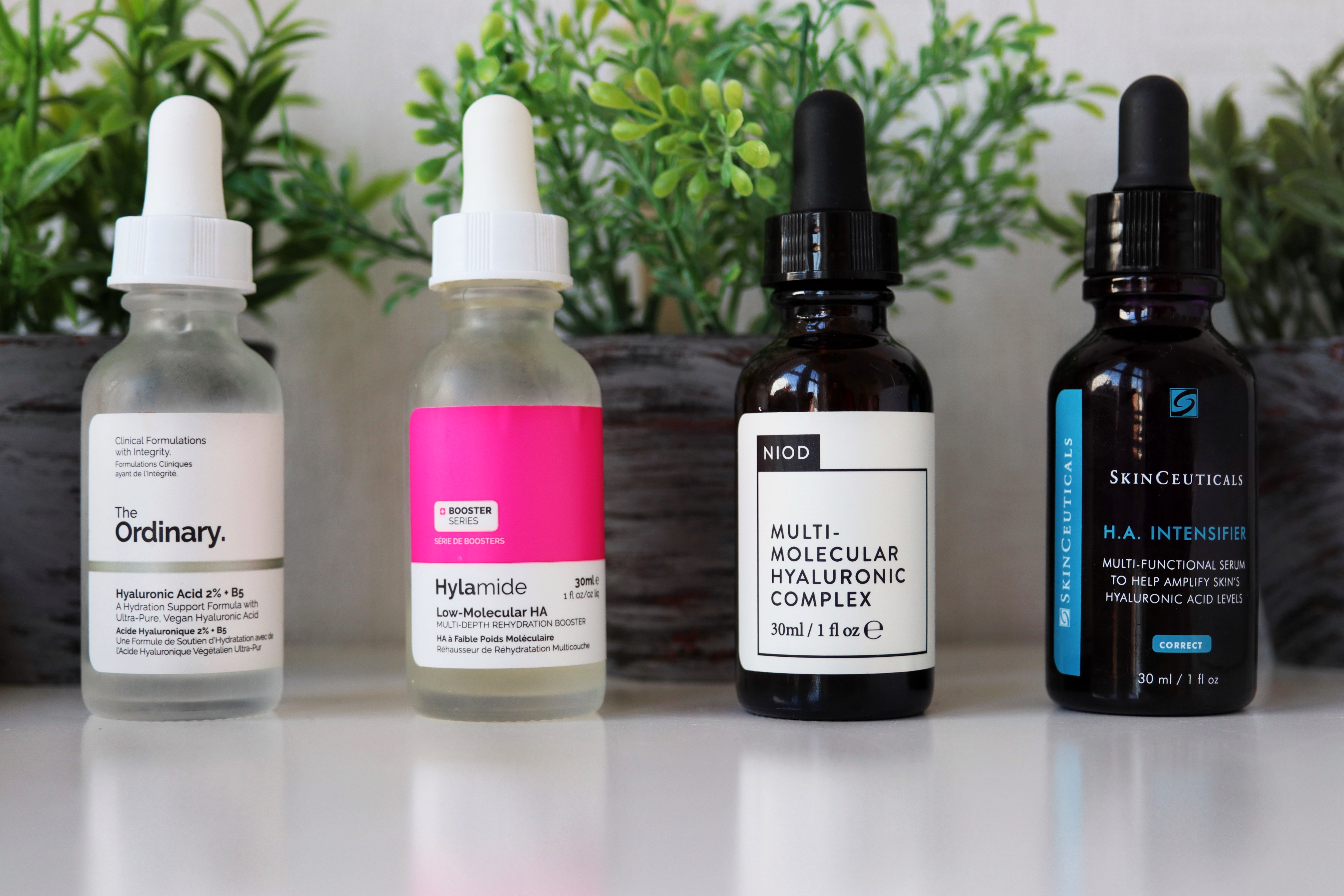 Four bottles of serums sitting on a white desk top. Behind the bottles, slightly out of focus. are three small herbs posts, green herbs in grey pots. The serum bottles from left to right are: The Ordinary hyaluronic acid (clear body, white label, black writing). Hyalmide hyaluronic acid, clear bottle, pink and white label, black writing. NIOD Muli-molecular hyaluronic acid, dark brown bottle, white label, black writing. Skinceuticals H.A Intensifier, Brown bottle, White and bright blue writing.
