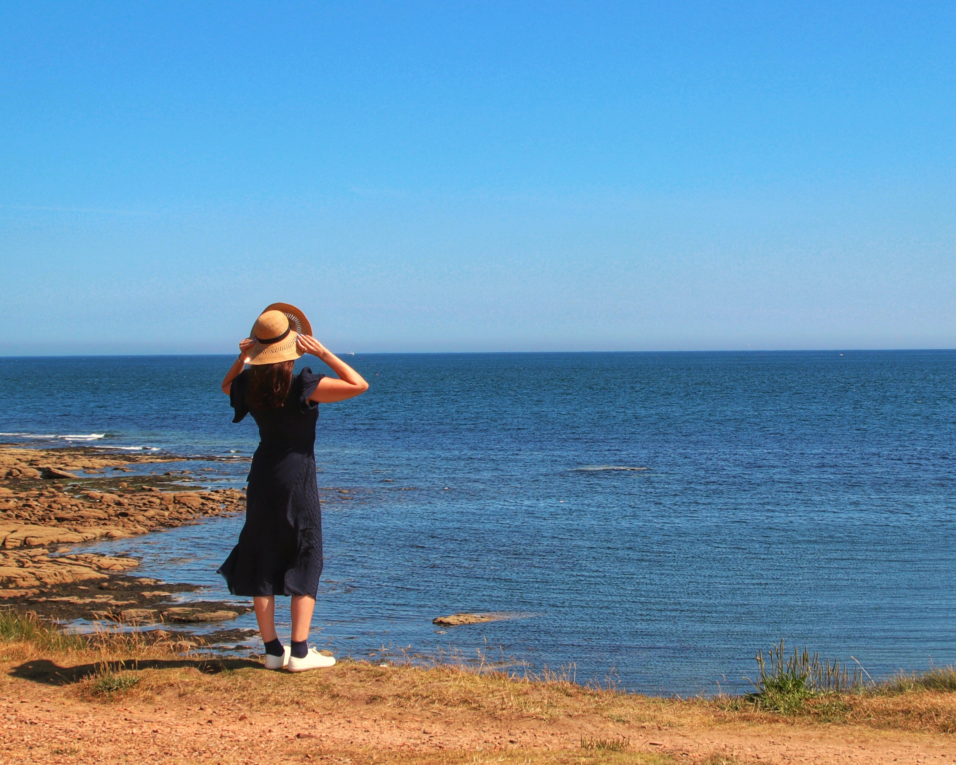 This image shows a woman over looking the coastline in Northumberland. She is standing on the top of the dunes wearing a blue dress and white trainers. It is a beautifully sunny day, with a breeze as she holds onto her sun hat with both hands. The sky and sea are beautiful tones of blue.