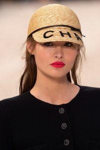 Makeup Looks image of a Brunette model wearing natural makeup and a bright raspberry lipstick. Model wears a black top with a round neck and black button with a straw cap with black bow and chanel in black ribbon.