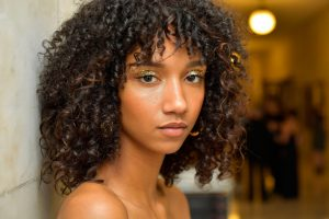 image of a Black model with natural makeup that enhances her features. Model wears a wash of gold glitter over her eyelids and a nude lipstick. Her hair is natural and shoulder length.