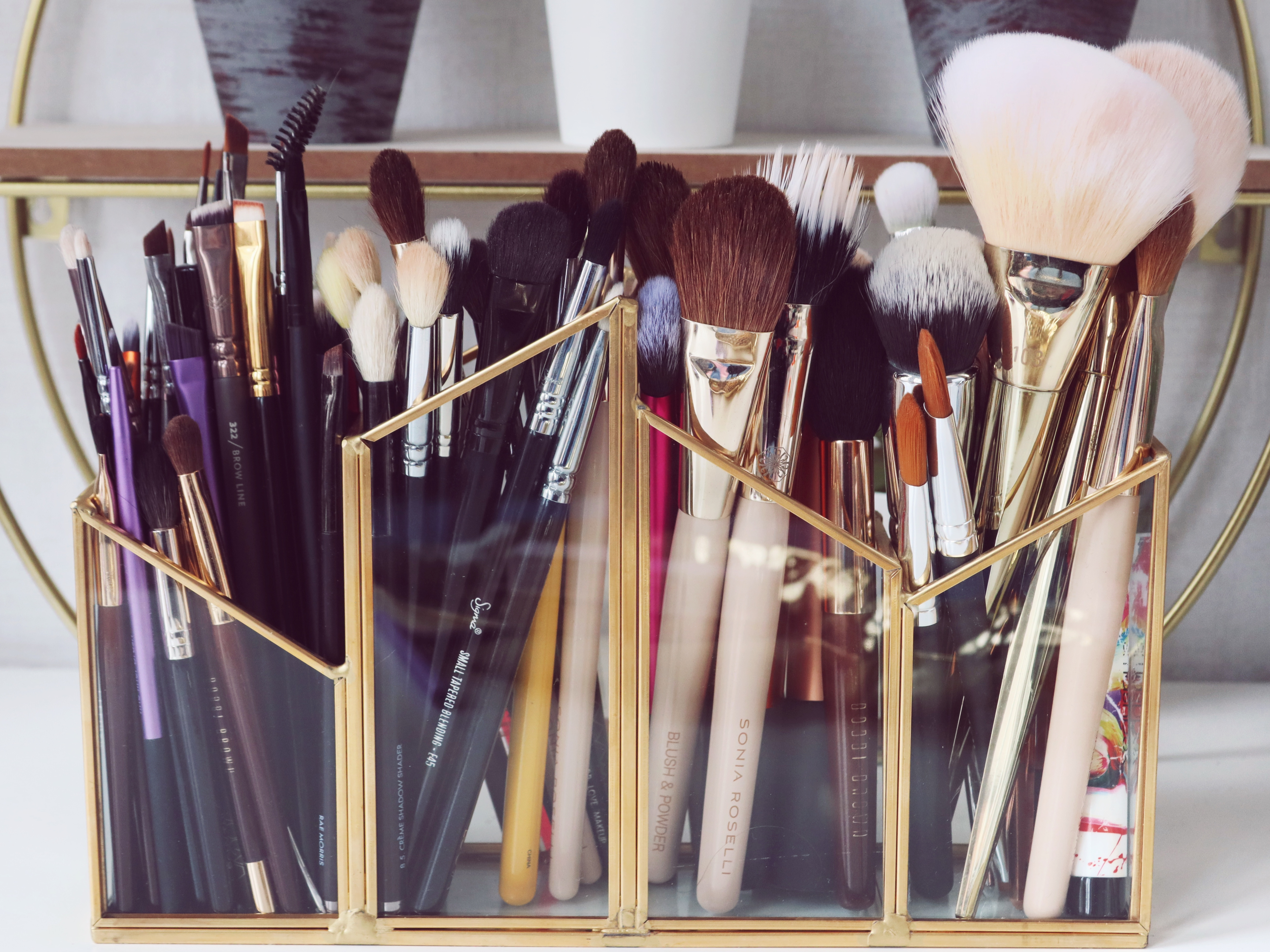 This image contains a glass brush container with gold edging that has sections. It is filled with makeup brushes, each sections filled with different types of brushes from lip brushes, eyeshadow, to face brushes. It sits on a white table top in front of a gold shelving unit and white wall.