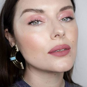 makeup looks images of a brunette female with white skin wearing pink glossy eye makeup and nude pink lipstick. Picture is a close up of her face.