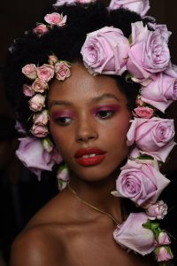 image of a Black model wearing vibrant pink eyeshadow and red lipstick. model has fresh roses in her hair.