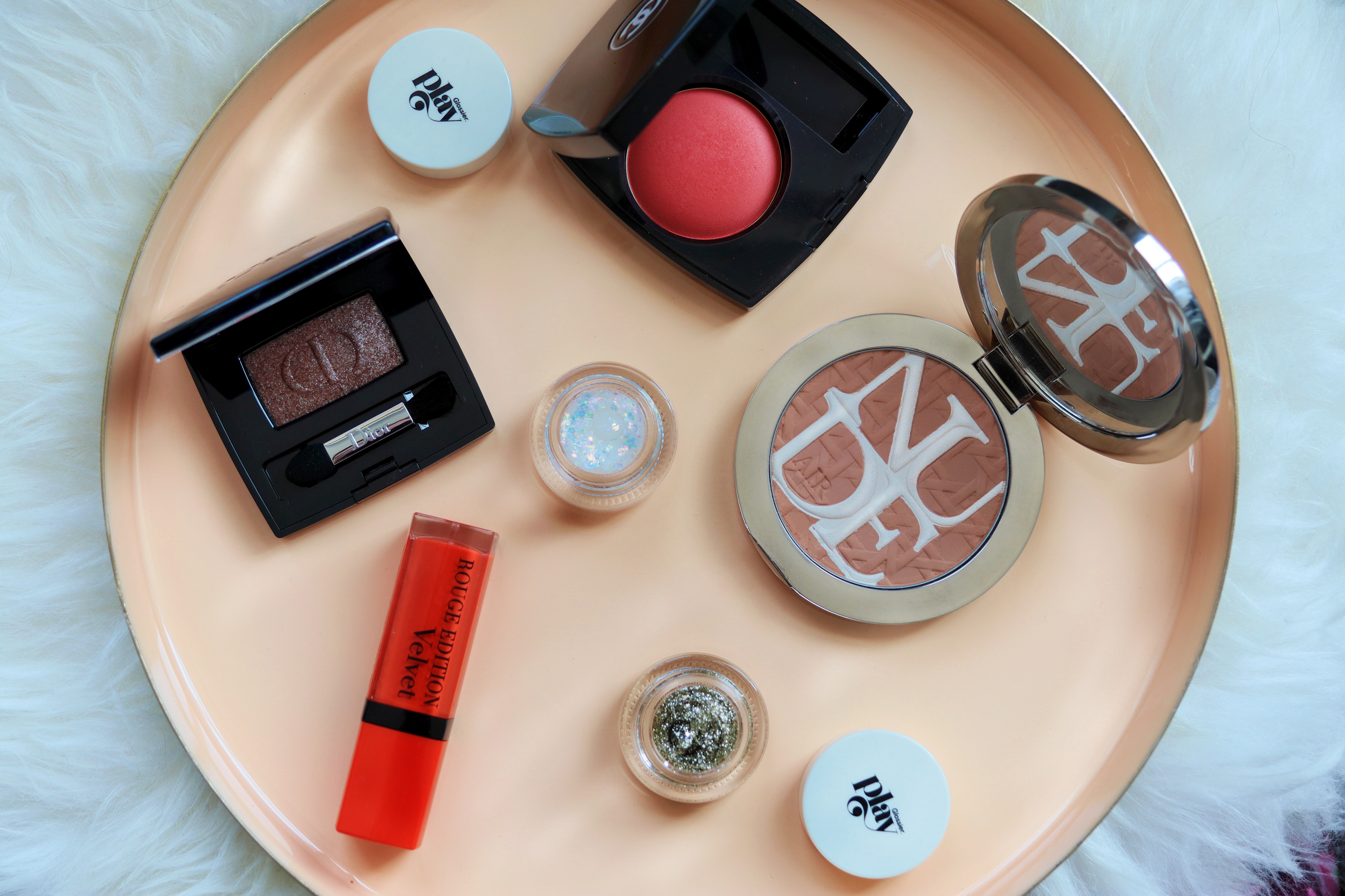 Image taken from above (birds eye view) of makeup set up on a peach tray. Tray is sat on a sheep skin rug. Makeup is formed to show makeup looks that can be created using different products. A bright red lipstick, glittery eyeshadow compact, two round pots of gel glitters and a bronzer in a silver compact with a mirror.