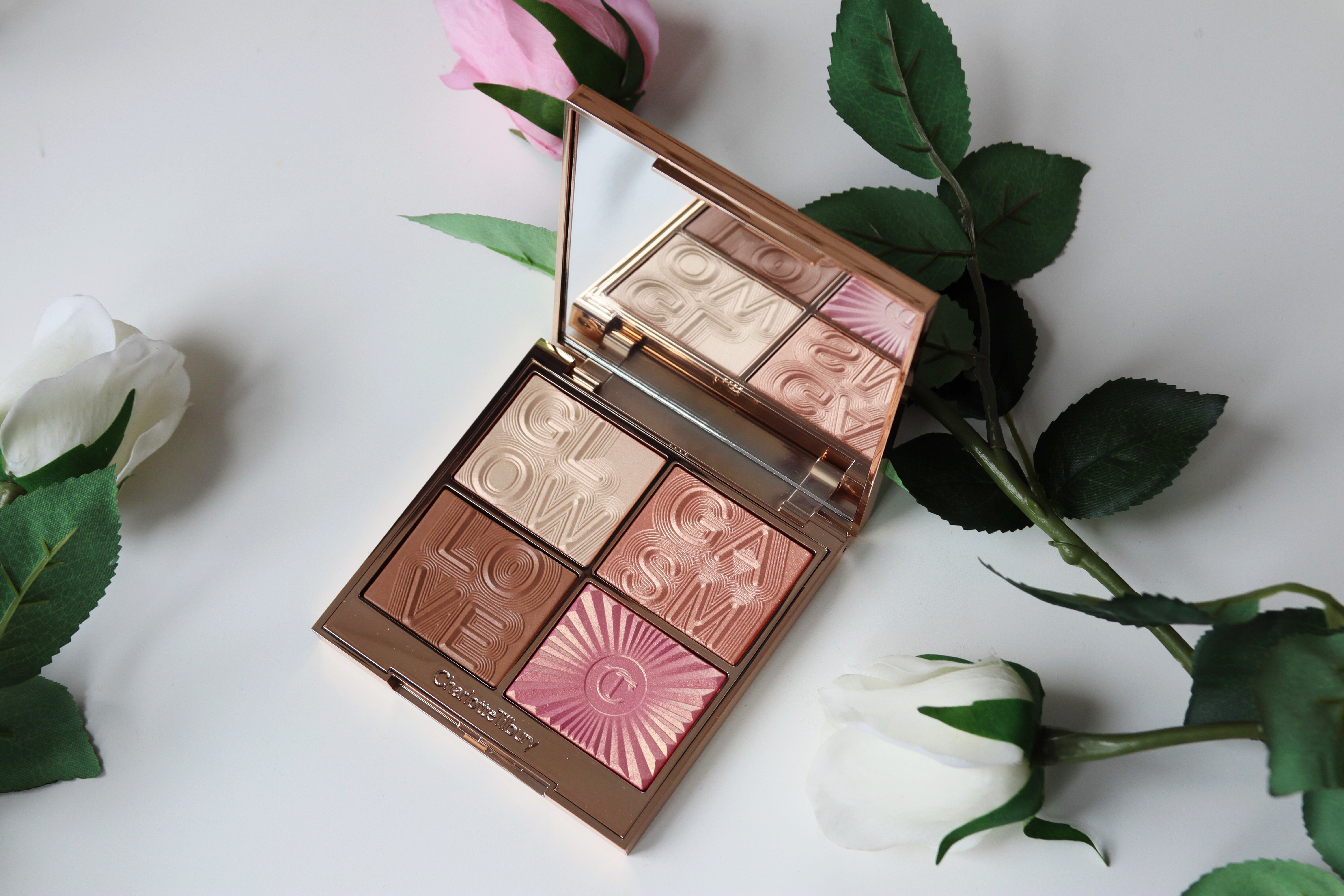 Charlotte Tilbury 'Glowgasm' palette sitting on a white background. The palette is open showing the four shades, a rose blush, two champagne highlighter shades, a neutral bronzer. They is a fake white rose to the right side of the palette just out of view.