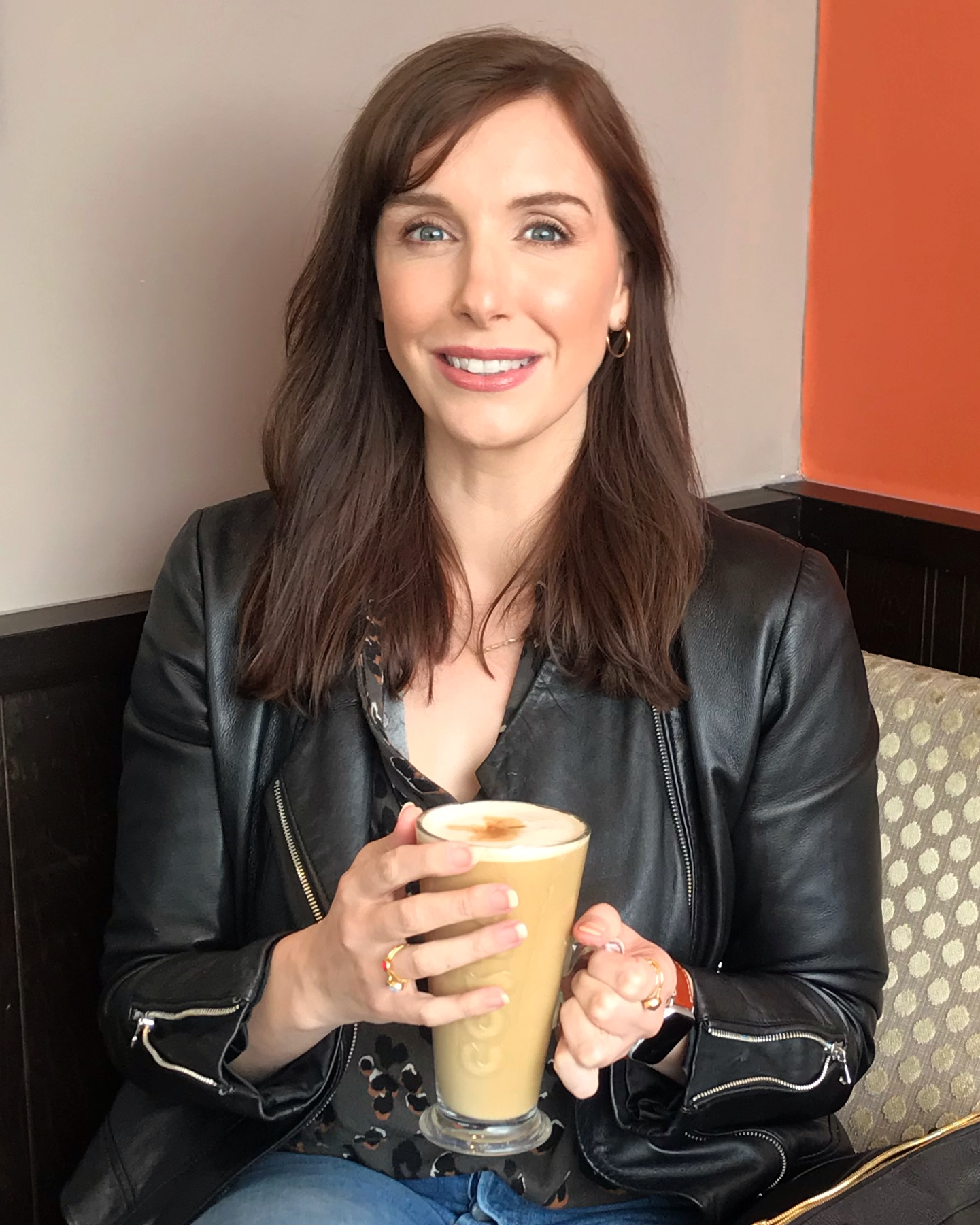 White female mid thirties, holding a cup of coffee. She is smiling and has dark brown shoulder length hair. She is sat down, in a manner to hint a conversational tone about being clumsy.