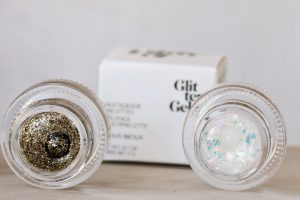 A review of Glossier Play glitters. The glitters face the camera. A gold glitter is on the left of the picture, on the right is a pearl.