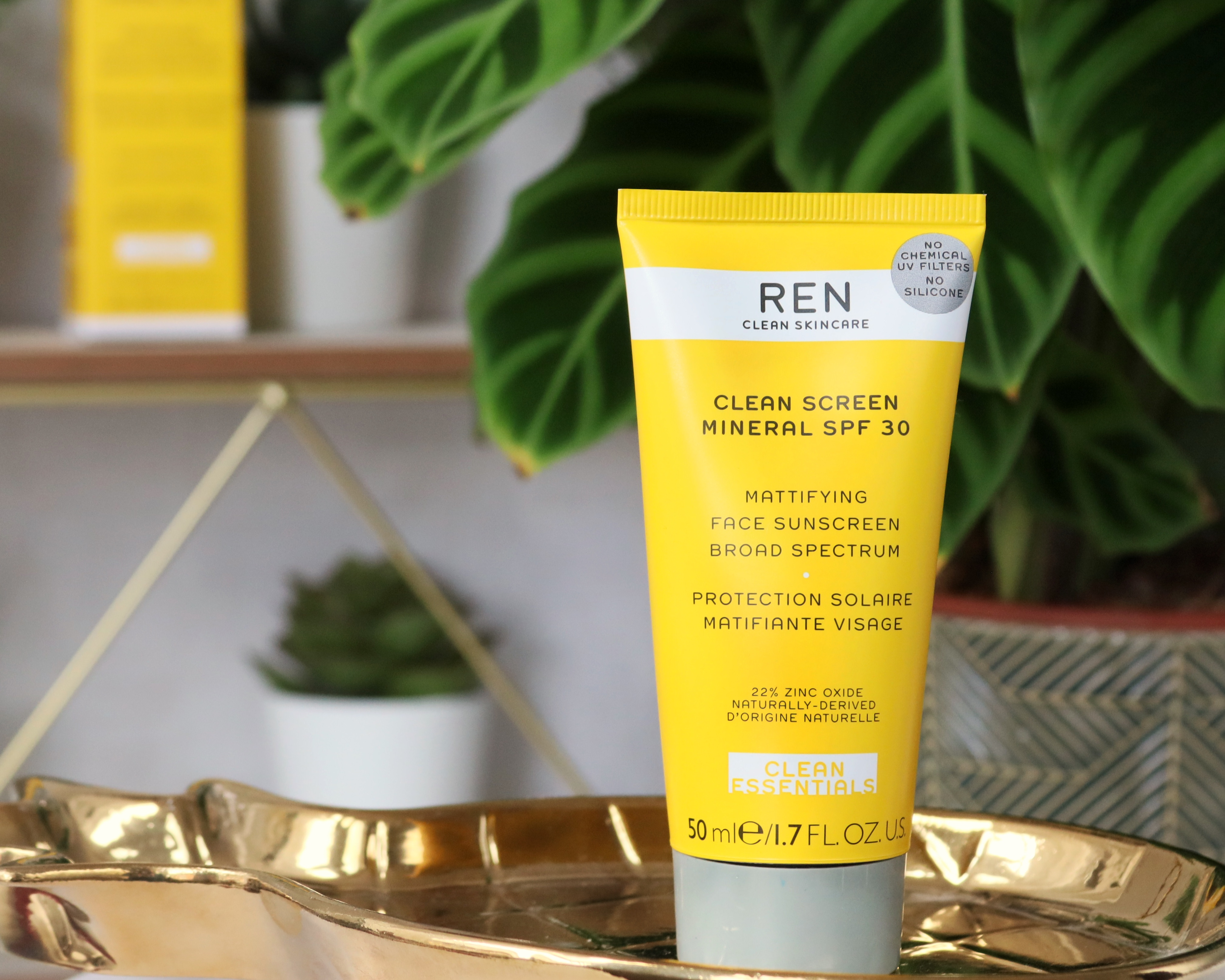 Clean Screen Mineral SPF30 from REN Skincare stood on a gold pineapple shaped tray. Blurred in the background is a plant and the skincare box. The SPF itself is in a squirty tube which is bright yellow with the brand name on and a grey lid.