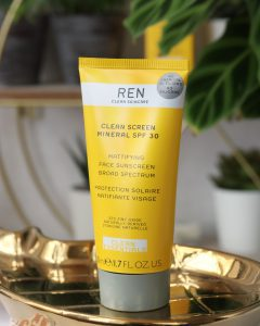 Mineral SPF30 from REN Skincare stood on a gold pineapple shaped tray. Blurred in the background is a plant and the skincare box. The SPF itself is in a squirty tube which is bright yellow with the brand name on and a grey lid.
