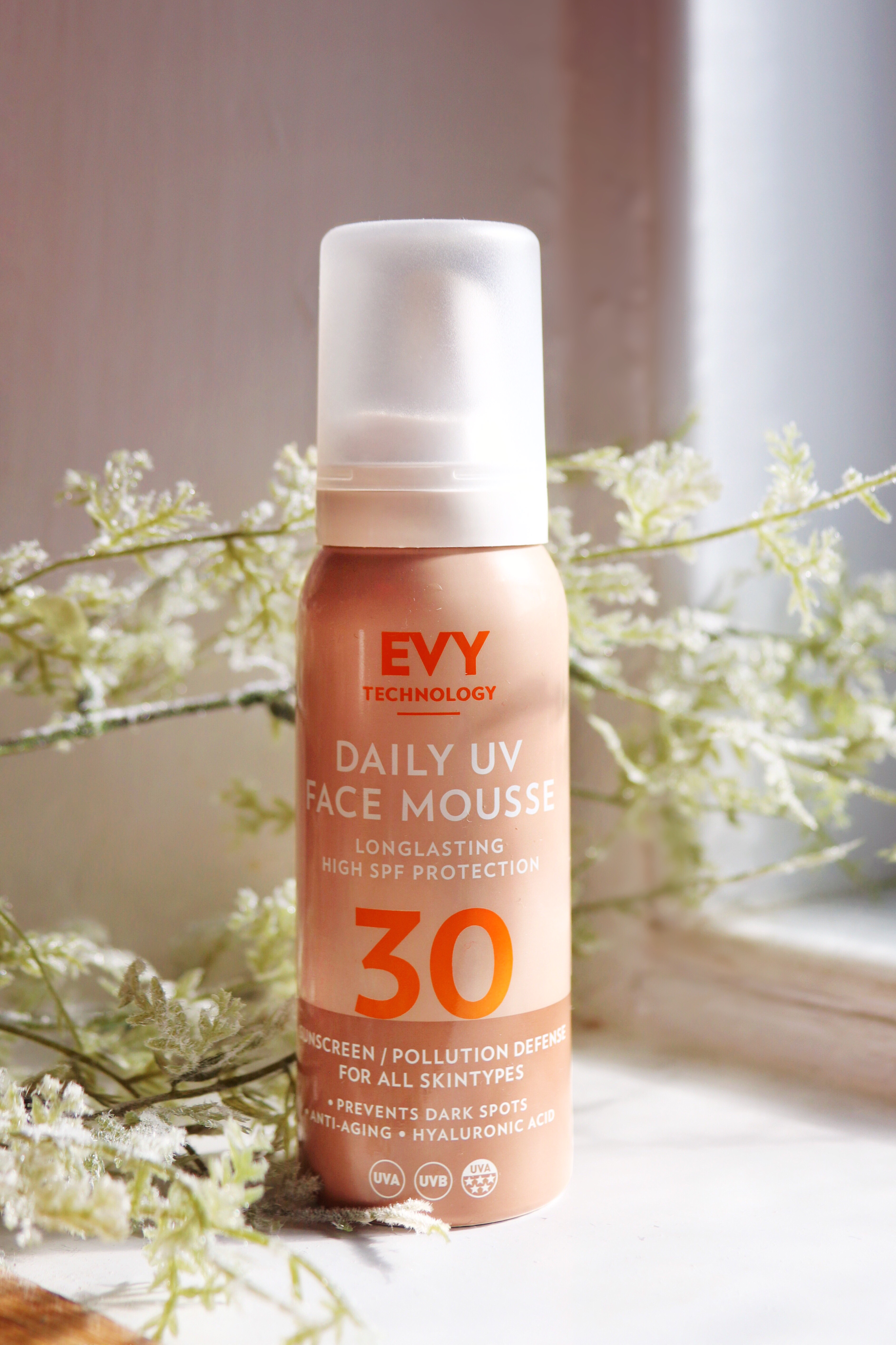 Aerosol can of a SPF. The can is two shades of tan brown, one lighter one darker and the lid is white. The logo is orange and reads 'EVY TECHNOLOGY' followed by 'DAILY UV FACE MOUSSE' in white. The can in sat on a white window sill with white and green spring flowers behind to decorate. The light is shining in from a window on the left out of picture.