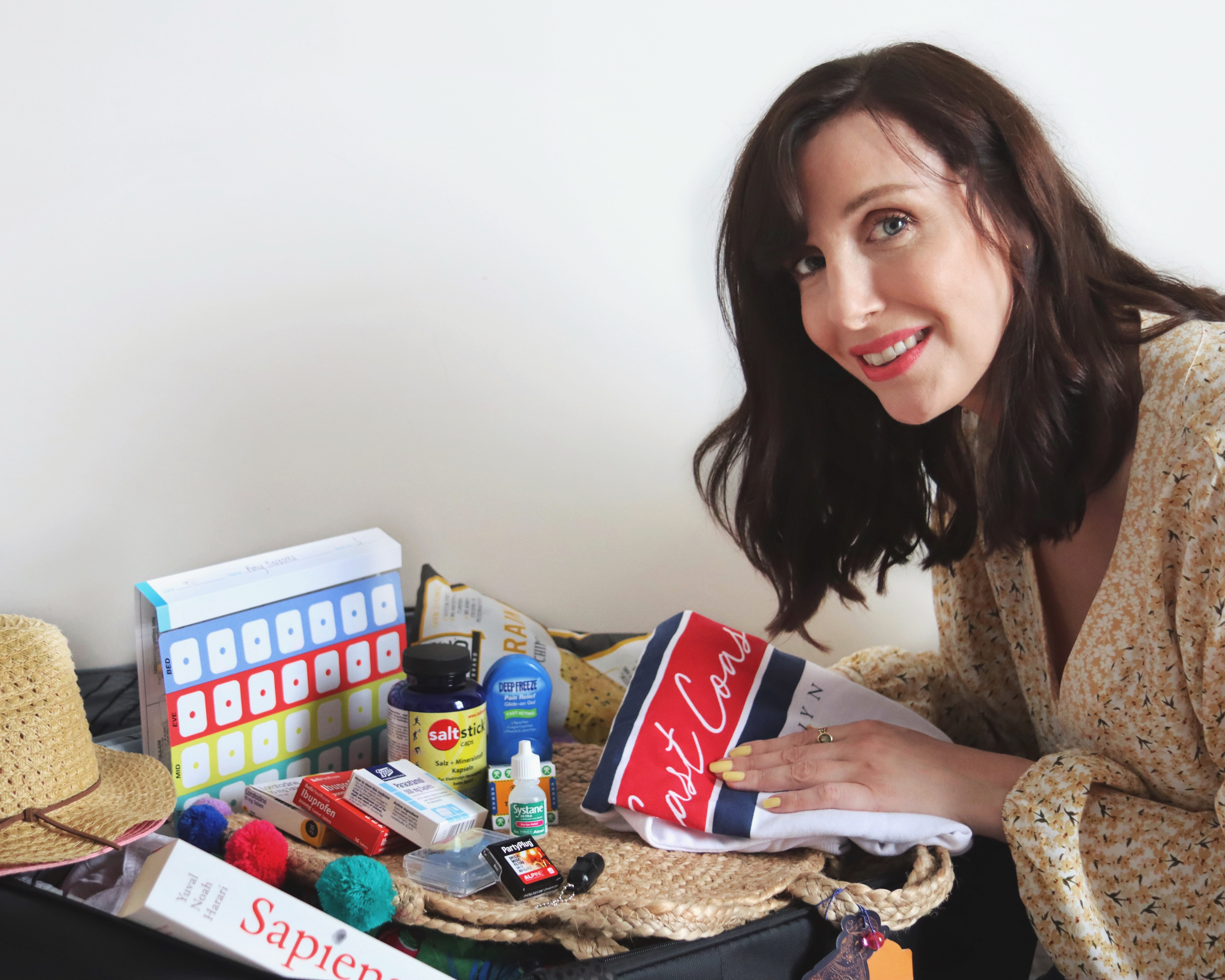 Holiday Care Package - Tips on what to take on holiday to be fully prepared when you're a Spoonie! Image of a woman with shoulder length dark hair packing a suitcase with medical goods.