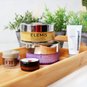 The Basics! Want to learn which cleanser is right for you? Then this post has you covered! This image has balm cleansers from Elemis, Clinique, dermelogica and Emma Hardie. They are all sitting on a wooden tray with greenery blurred in the background.