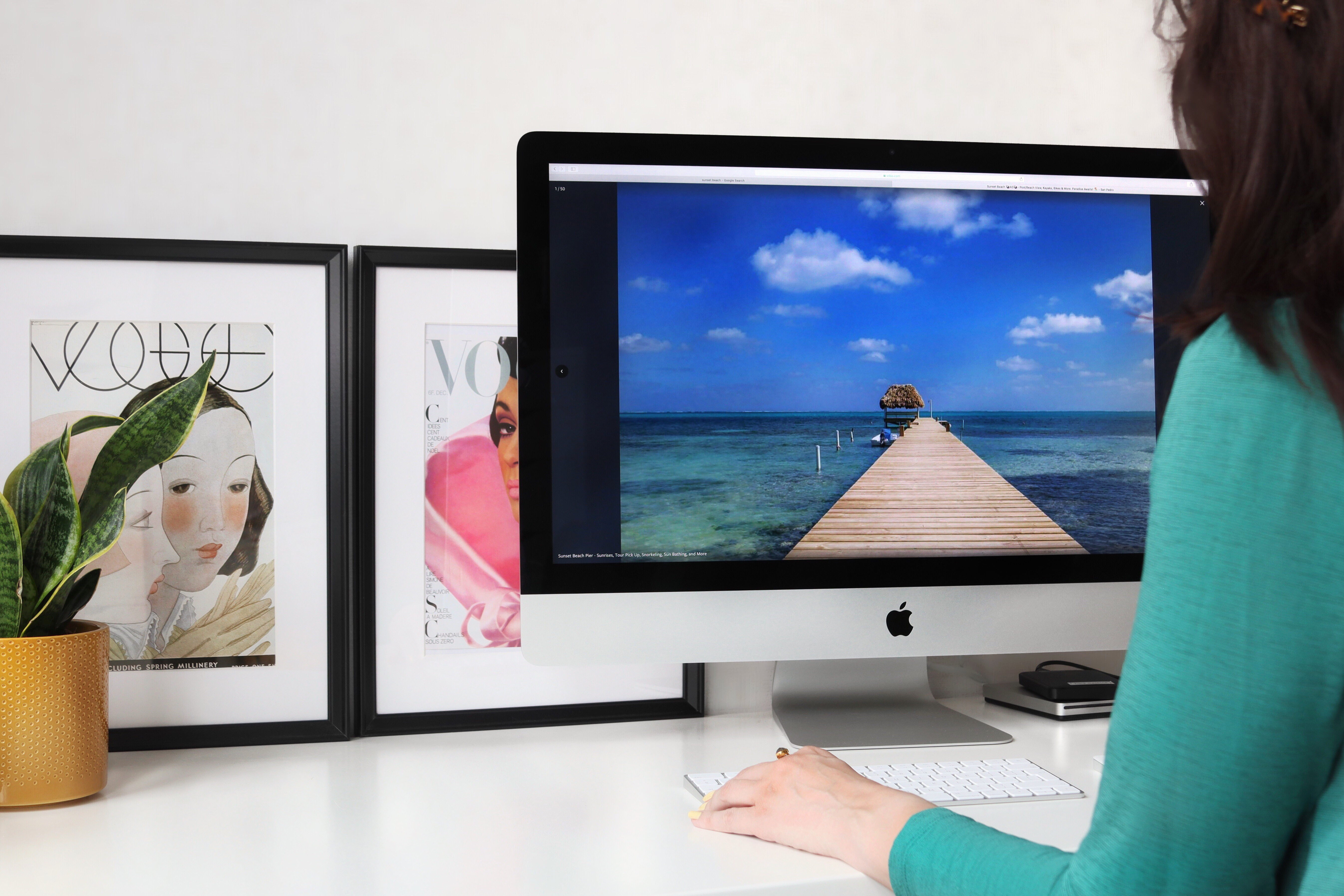 Travelling with chronic illness - tips for planning a holiday. Image of a Female sitting at at a desk in front of a computer looking at a holiday destination.