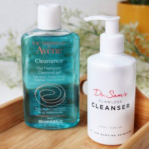 Cleansing - The Basics! Want to learn which cleanser is right for you? Then this post has you covered! This image is of two gel cleansers one by Avene in a see through bottle-the cleanser is a teal blue. The second cleanser is a in white opaque bottle by 'Dr Sam'. The bottles sit on a wooden tray with greenery blurred in the background.