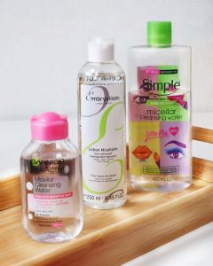 Cleansing - The Basics! Want to learn which cleanser is right for you? Then this post has you covered! This image is of Micella waters from garner, embroylisee and simple. The clear bottles sit on a wooden tray with a white background with the sunlight reflecting through.