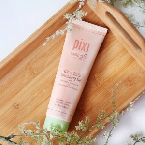 Cleansing - Skincare basics - Pixi exfoliating gel laid on a wooden tray.