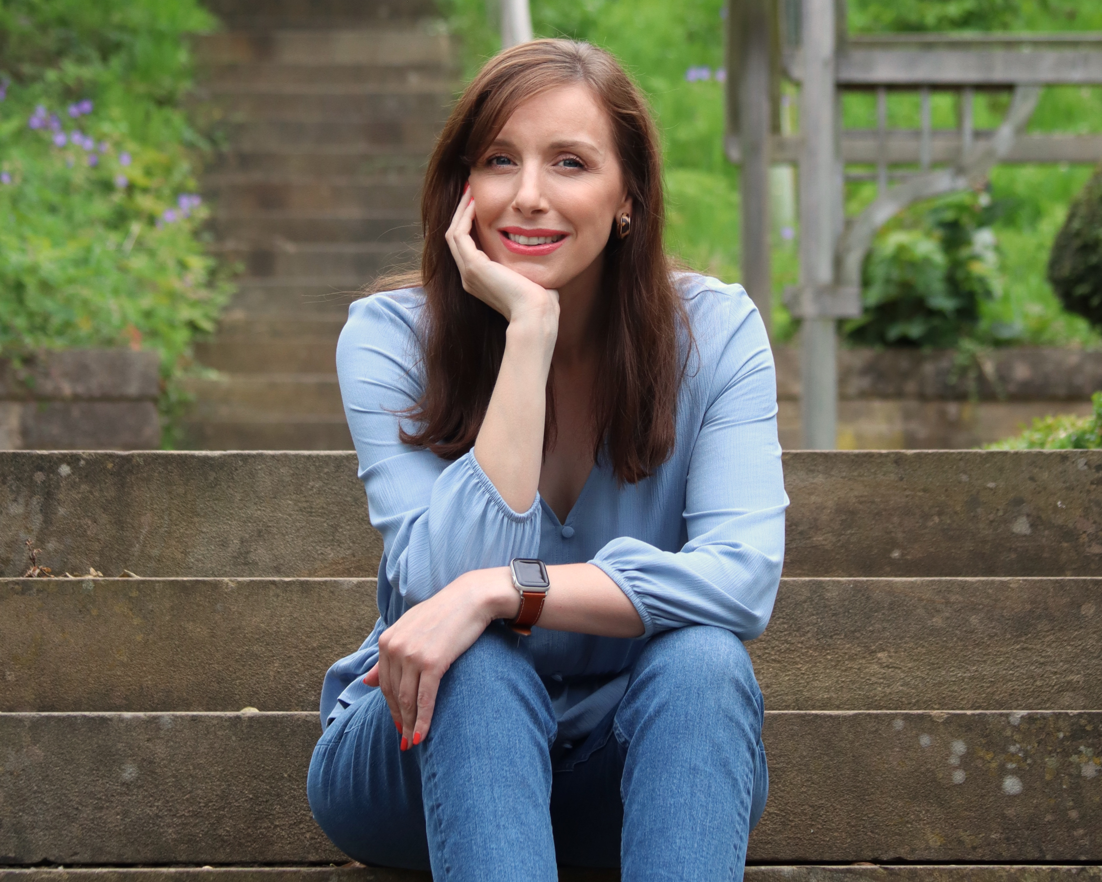 A year of survival - facing birthdays with chronic illness. Female woman sits on steps outside looking towards the camera smiling. She has brown hair and fair skin and is wearing a light blue top and blue jeans.