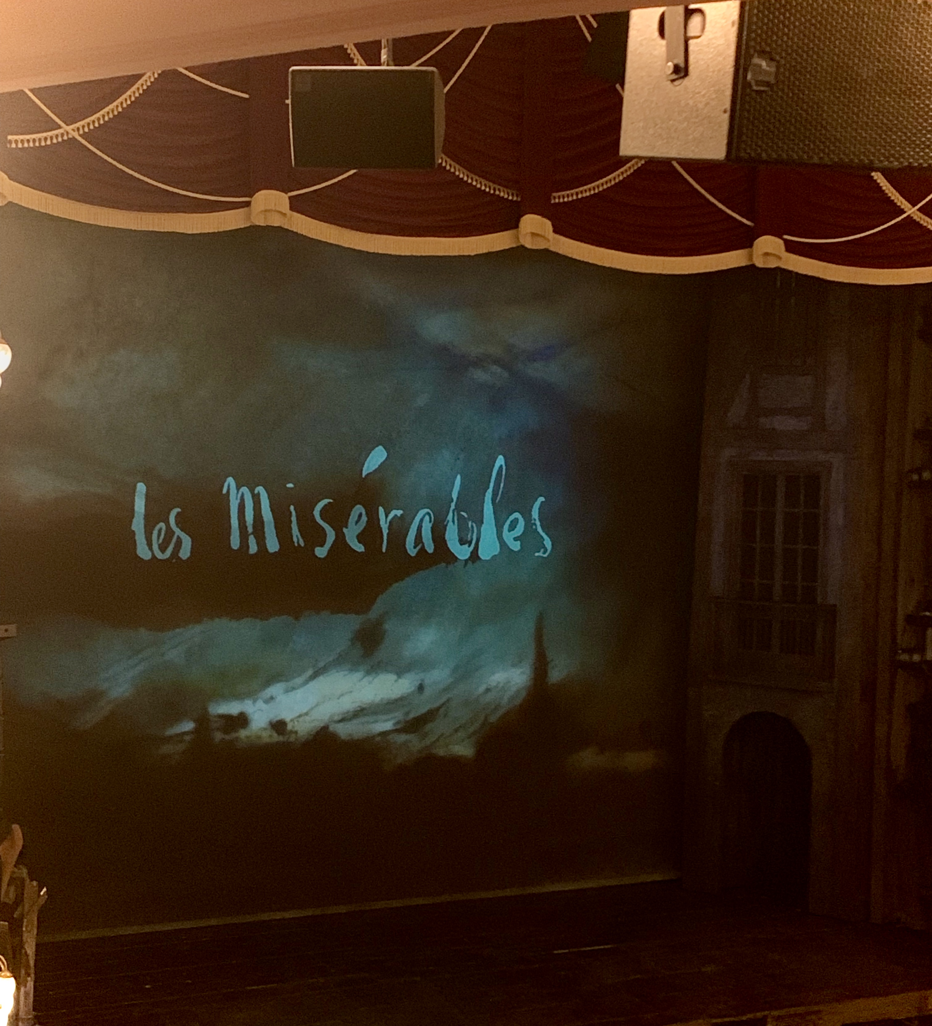 Les Miserables Review - Newcastle Theatre Royal. Image of the stage at the Theatre Royal with a curtain hanging showing the title 'Les Miserables'. The red curtain is raised ready for the performance.