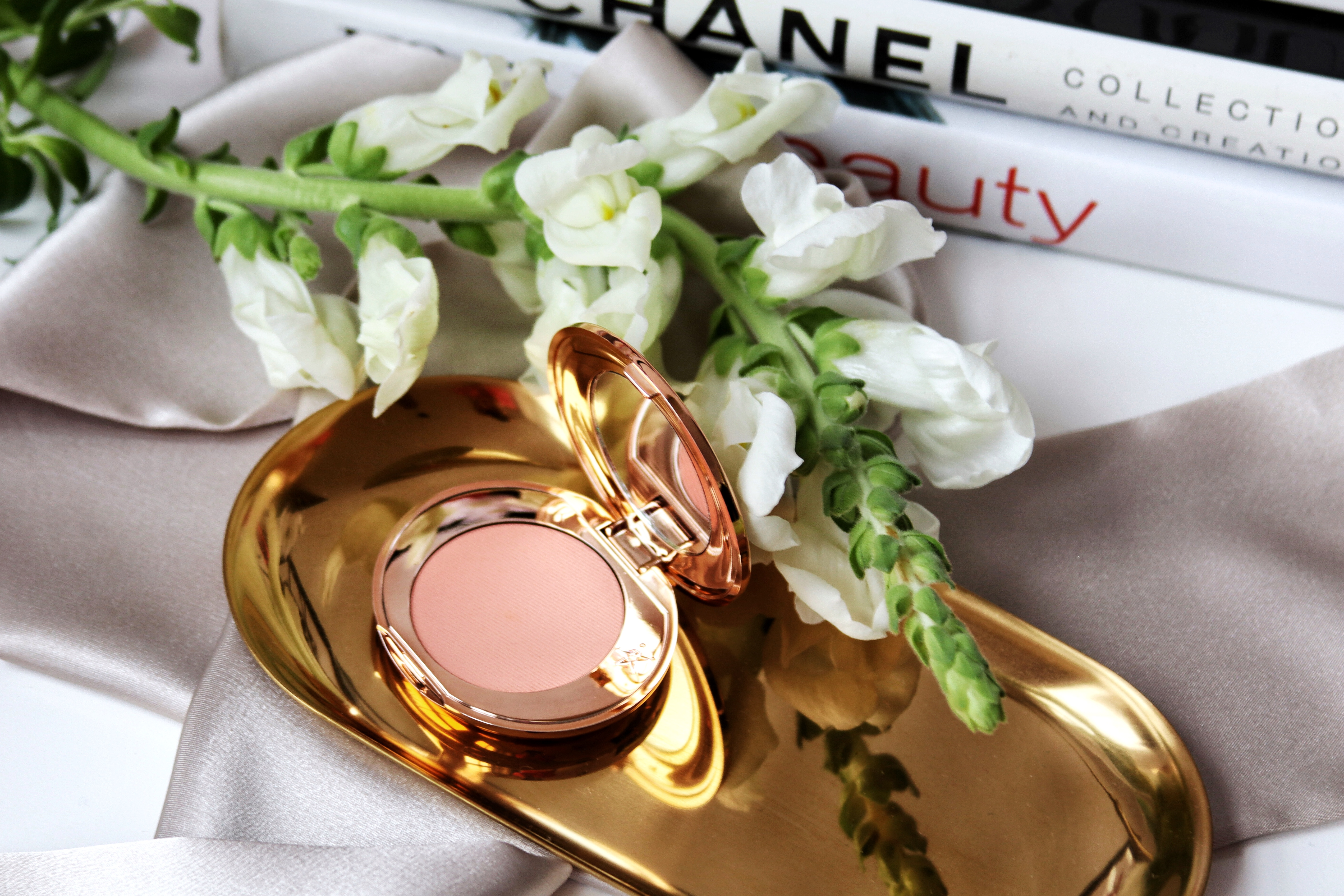 Image of makeup by Charlotte Tilbury on gold tray with books in the background. Makeup being reviewed is called 'Magic Vanish'.
