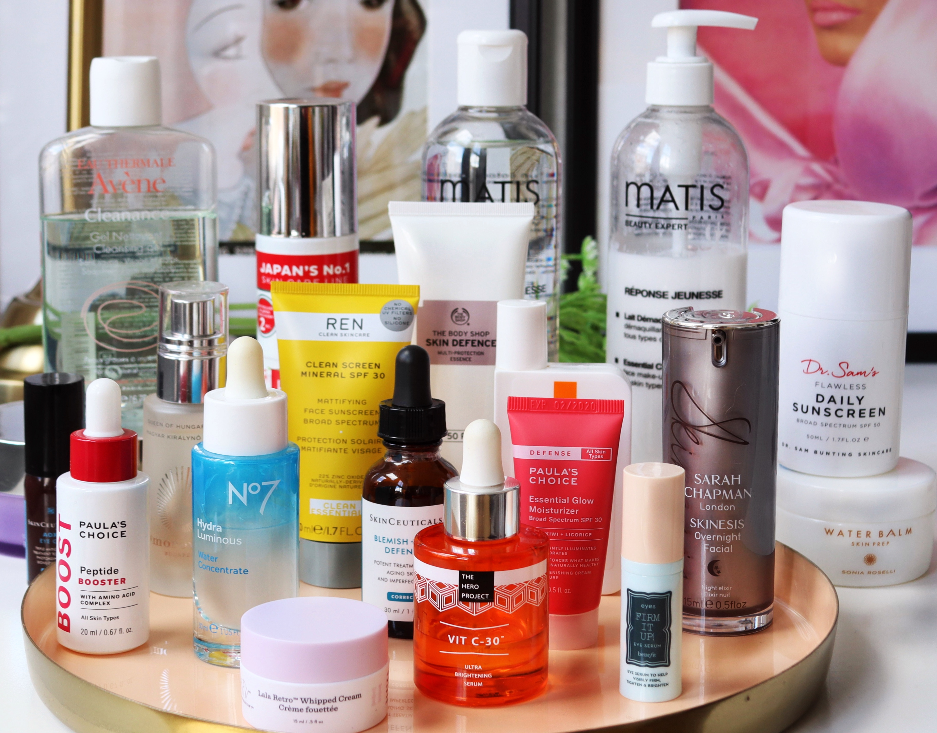 Skincare routine : We all want a perfect, easy one, in this post I'm talking about how to build a basic one. Once you've got that sorted you'll see big changes in your skin and be ready to add more products in should you wish! Image of many items on skincare placed on a tray which is sitting on a desk as examples of items you can choose for a skincare routine.