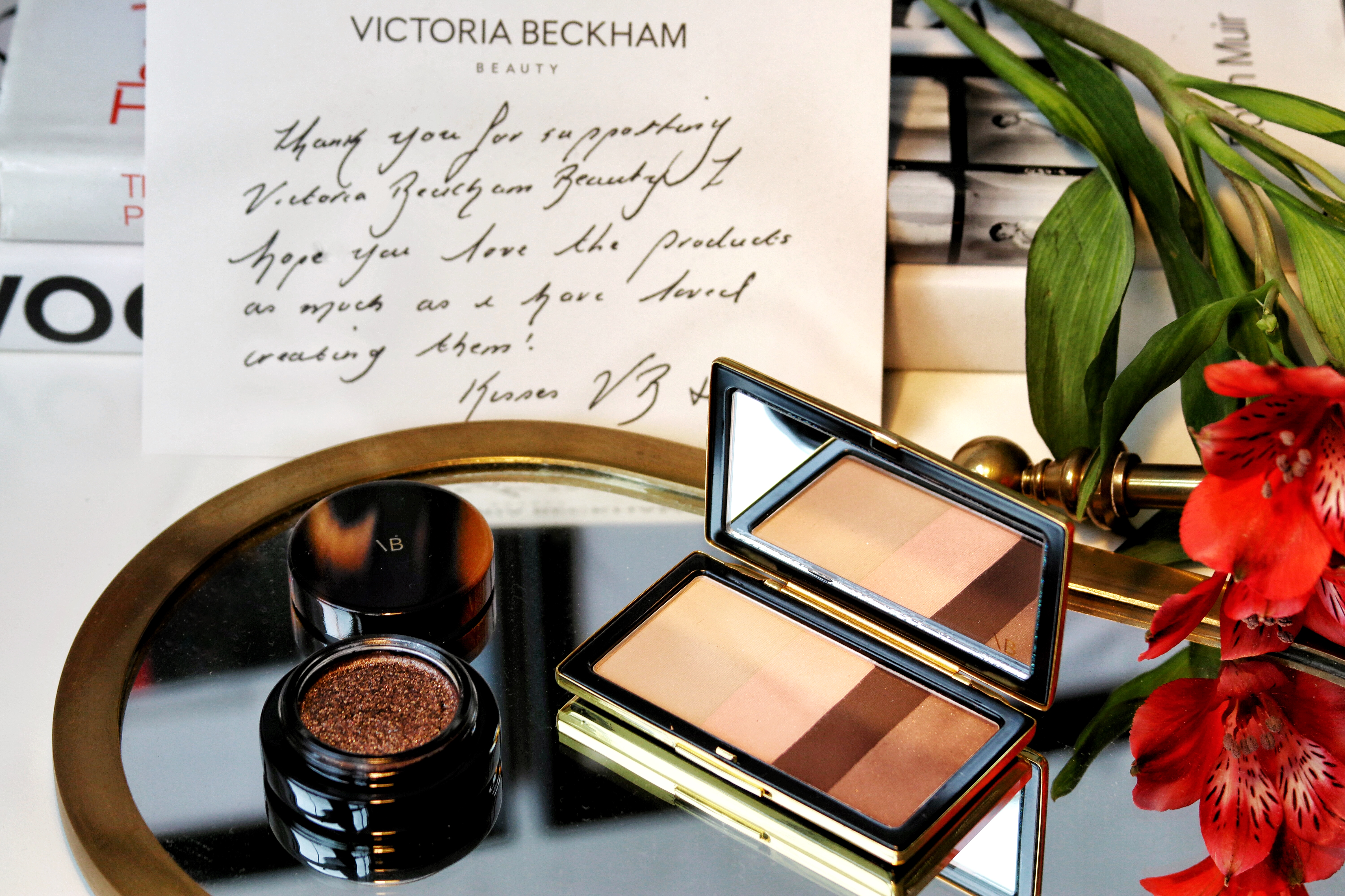 Victoria Beckham Beauty - A review of the latest makeup launch from this former Spice girl. It's clean beauty, it's sustainable and it's gorgeous! In this image the smokey eyeshadow palette sits open on a mirror, as does the glitter lid lustre. Behind them is a hand printed note from VBB, red flowers frame the photo.