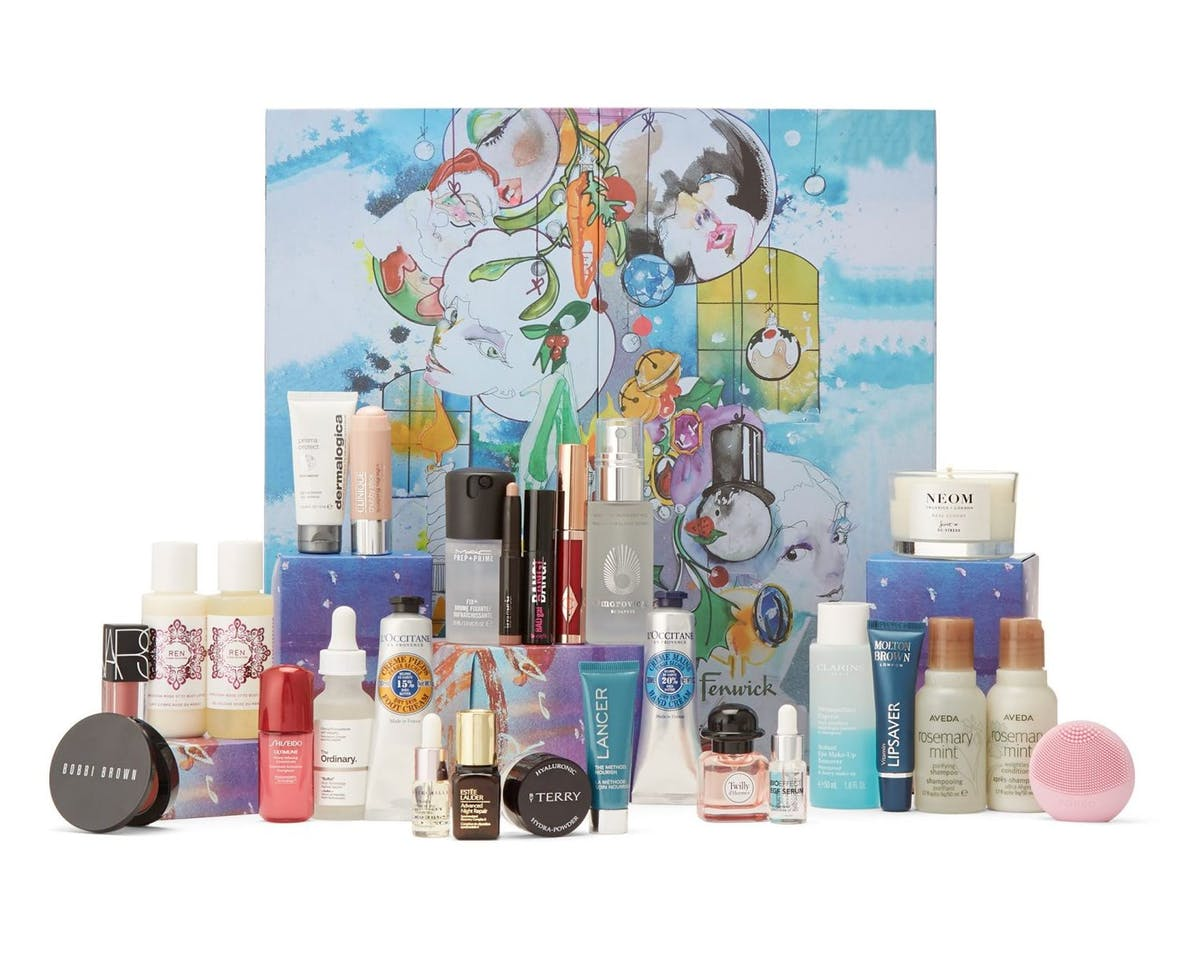 Fenwick Beauty Advent Calendar 2019 - 25 beauty products stand in front of a box painted like the sky, blue with white clouds. Faces are painted onto baubles which hang in the middle of the box.