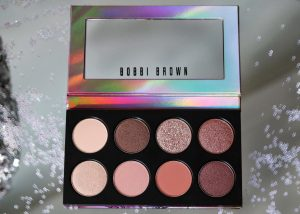 Bobbi Brown Love In The Afternoon eyeshadow palette sits on a mirrored surface surrounded by sequins. The post is filled with 5 makeup ideas that can be created from this palette.