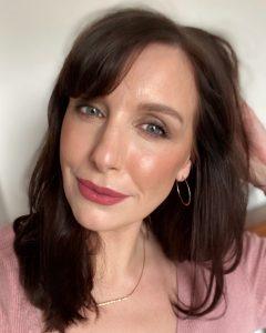 A woman with brunette hair wears a pink matte lipstick