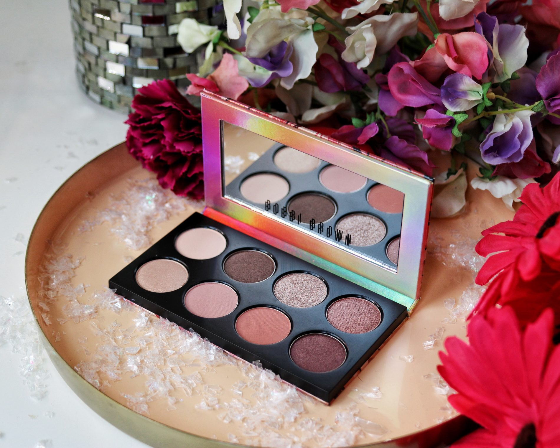 Bobbi Brown Love In The Afternoon Eyeshadow Palette! A beautiful collection of nude and berry eyeshadows sit in a palette on a pink tray surrounded by pink flowers. This post contains party and winter makeup looks.