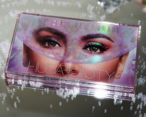 Huda Beauty Mercury Retrograde Eyeshadow Palette! Perfect for all party xmas makeup looks! Image of the eyeshadow palette which is holographic, sits on a mirrored surface surrounded by sequins.