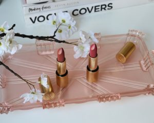 Lisa Eldridge velvet lipsticks in 'beauty' and 'muse'. A pink rose and brown matte in a gold case sits on a pink glass shelf. Behind it are white flowers and a stack of books blurred.