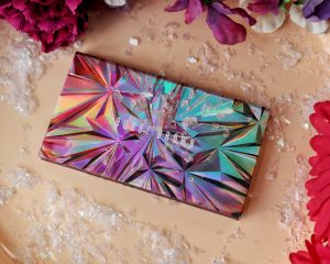A post on party makeup looks for the festive season. This image is of the Bobbi Brown love in the afternoon palette with is a holographic starburst pattern in multicolours. The palette sits on a pale pink tray covered in glitter and surrounded by flowers.