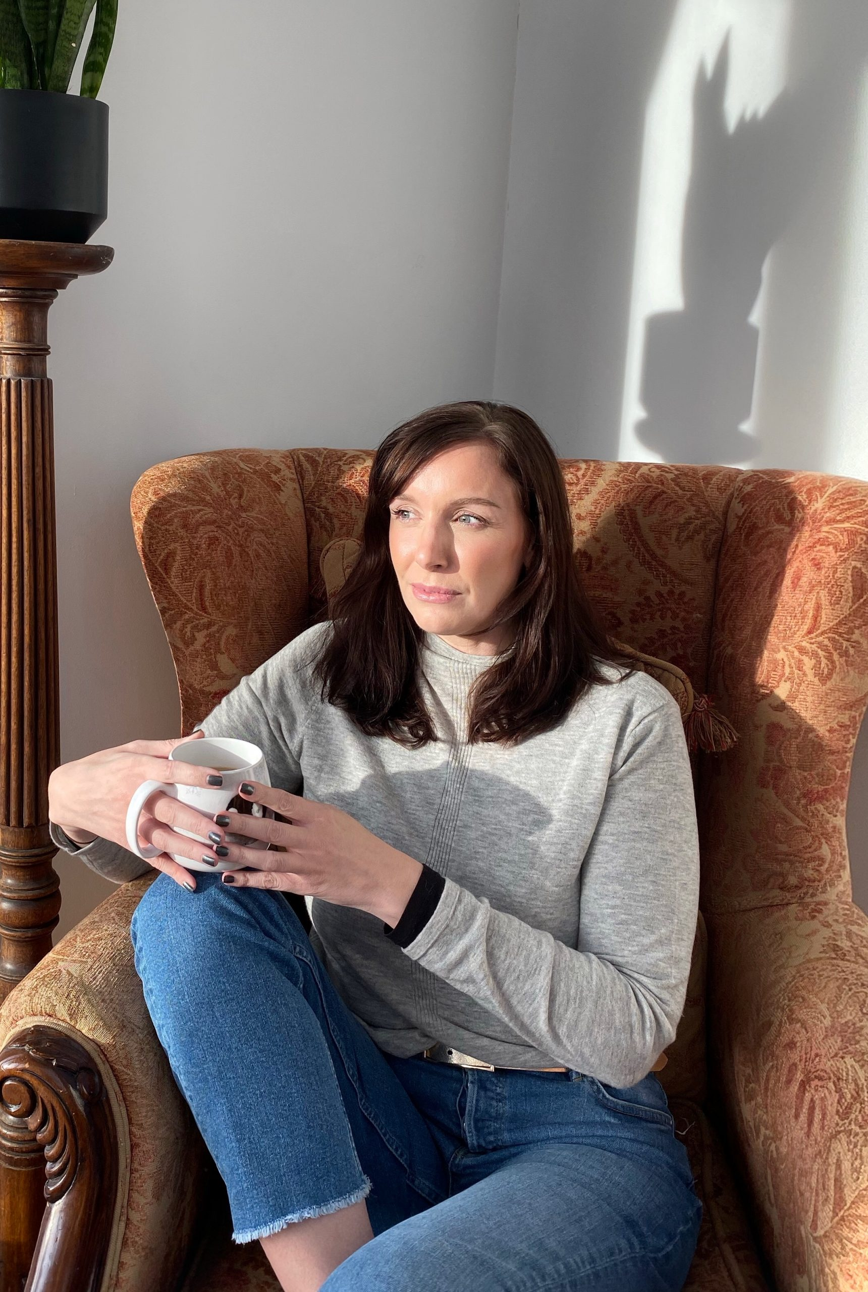 Woman with brunette shoulder length hair sits in an air chair looking aside while holding a cup of tea which is supported on her knee.