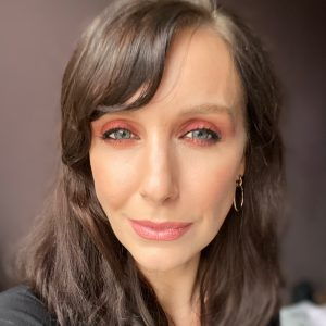 Winter makeup look, rusty red berry smokey eye on a brunette fair skinned woman with blue eyes.