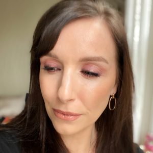 Christmas party makeup ideas using the Huda Beauty Mercury Retrograde eyeshadow palette. This fair skinned, brunette woman wears a lilac smokey eye look.
