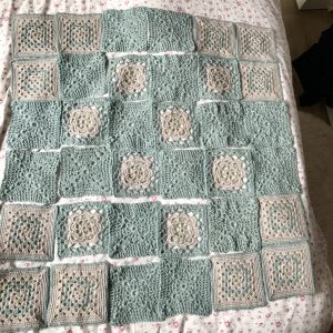 Placing of squares. They are in green, beige and mink. The squares will form a crochet blanket once stitched together.