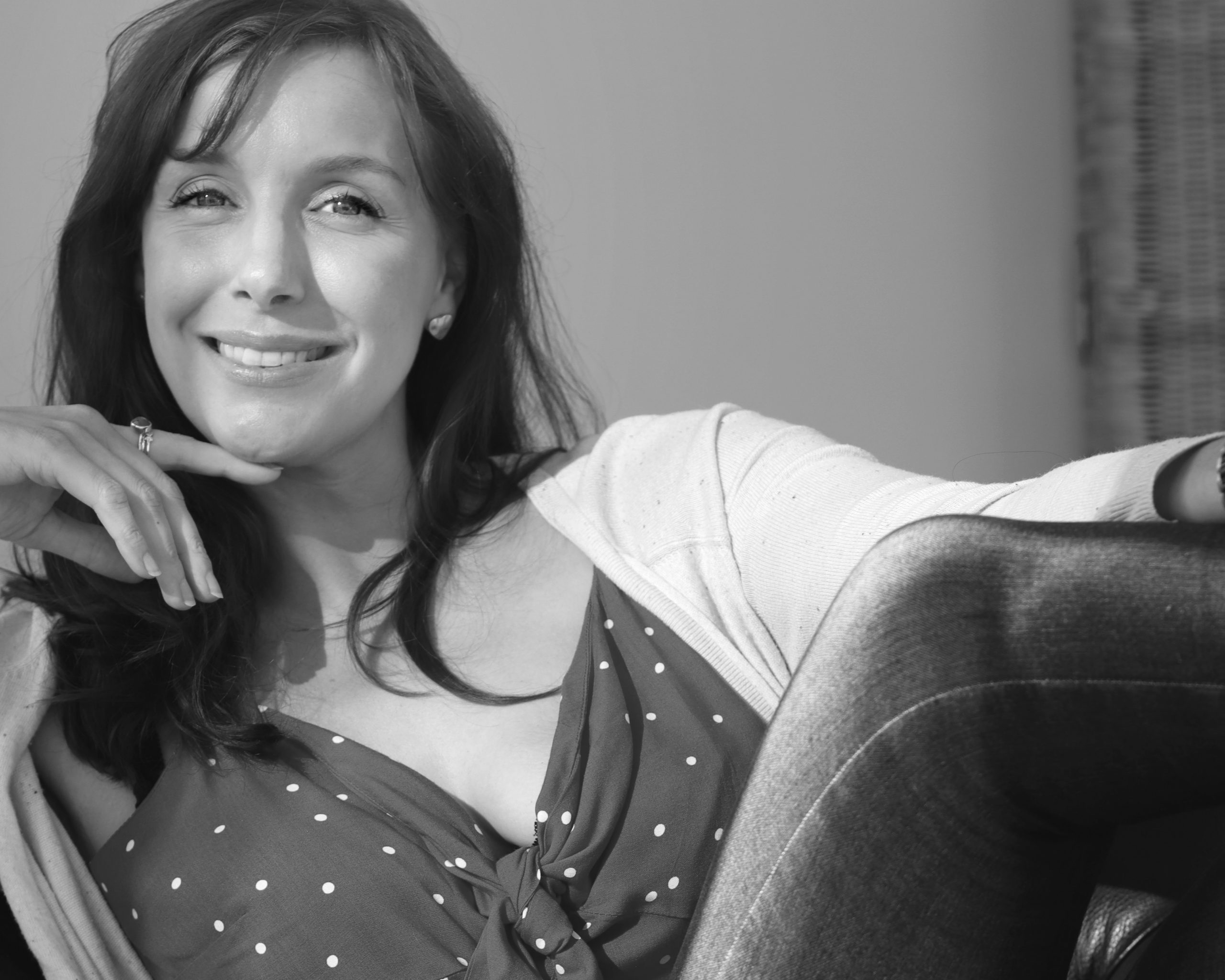 Amy's Chapter, welcome to my blog - Amy sits smiling at the camera. She is wearing a polka dot top and a white cardio and jeans. The image is in black and white.