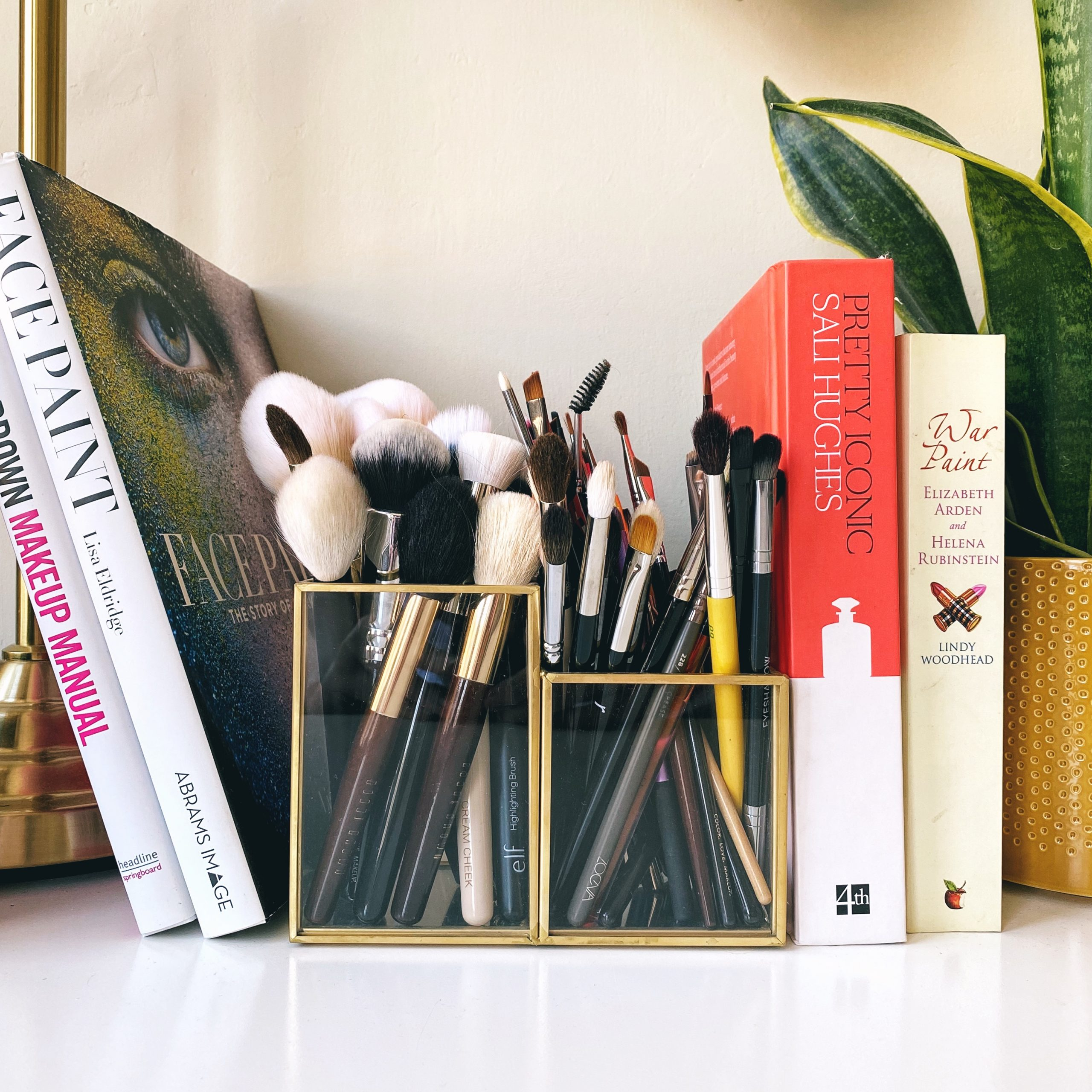 Makeup brush cleaning tips! A large tub of clean makeup brushes sit on a desk surrounded by makeup books and a plant.