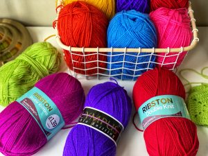 Balls of wool / yarn is vibrant rainbow colours laid on a table and in a basket