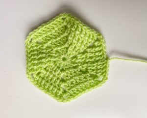 'How to' guide crochet hexy in a vibrant green on a white table.