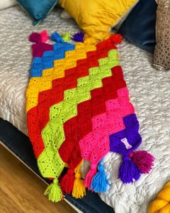 Beautiful, bright, easy crochet pattern. Children blanket in rainbow colours laid on a bed.
