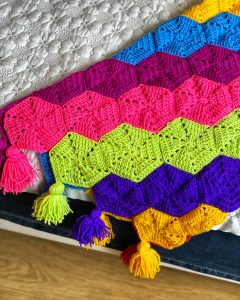 Bright crochet hexagon's joined together to make a colourful throw.