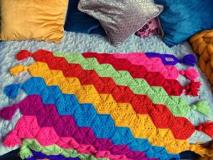Rainbow kids hexy crochet blanket laid out on a bed.