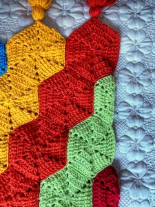 crochet hexy blanket laid on a bed with half hexy to make a straight edge and matching tassels. Colours are in green, orange, yellow and blue.
