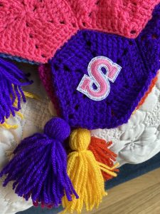 Personalised blanket! A letter 's' is shown, stitched onto the corner of a blanket. The letter is pink, the blanket corner is purple.