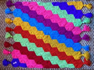 A bright coloured children's crochet blanket laid on the floor to show the pattern. This is to help anyone following the pattern see how to join the pieces together. It is an easy crochet hexy pattern.