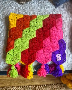 A rainbow homemade crochet afghan laid, folded on the bed. It is bright, rainbow colours and has a 'S' stitched onto the corner.