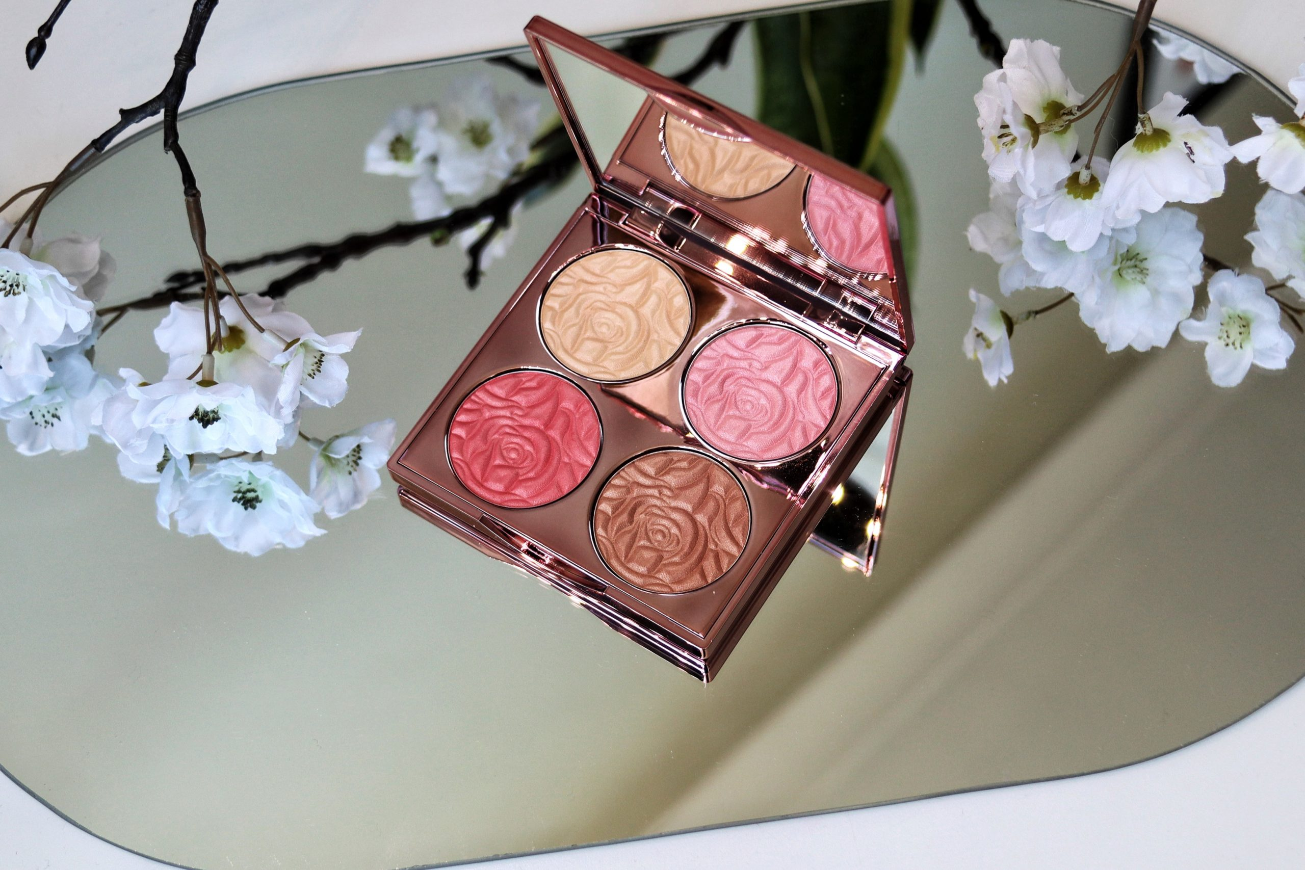 By Terry Brightening CC Palette. Image of a highlighter and blush palette on a mirror with white flowers surrounding it.