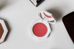 Fenty cream blusher sits on a white table, the product is open to show the shade.